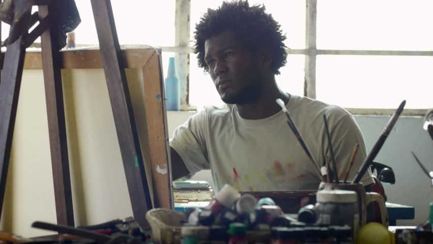 Young black people painting for hobbies. Proud african american man working as professional painter, skillful Cuban artist in art studio near table full of equipment, tools, canvas and paint
