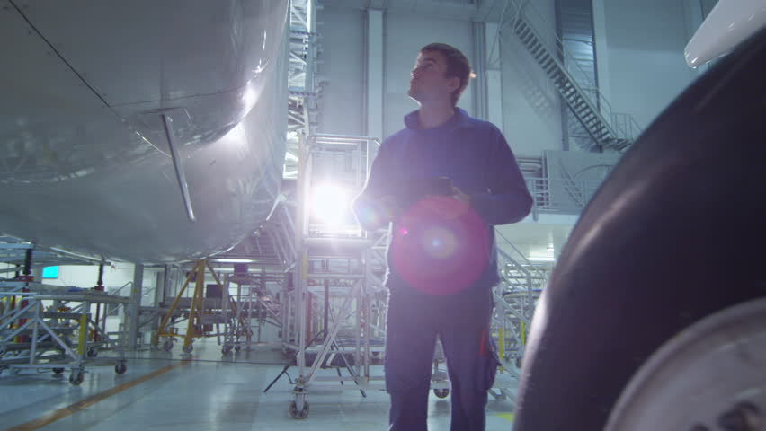 Aircraft maintenance mechanic uses tablet to inspect plane body in a hangar. Shot on RED Cinema Camera in 4K (UHD).