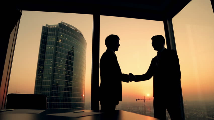 Silhouette of two businessmen talking and shaking hands standing by the window at sunset, the construction of a skyscraper and crane in the background | Shutterstock HD Video #12178793