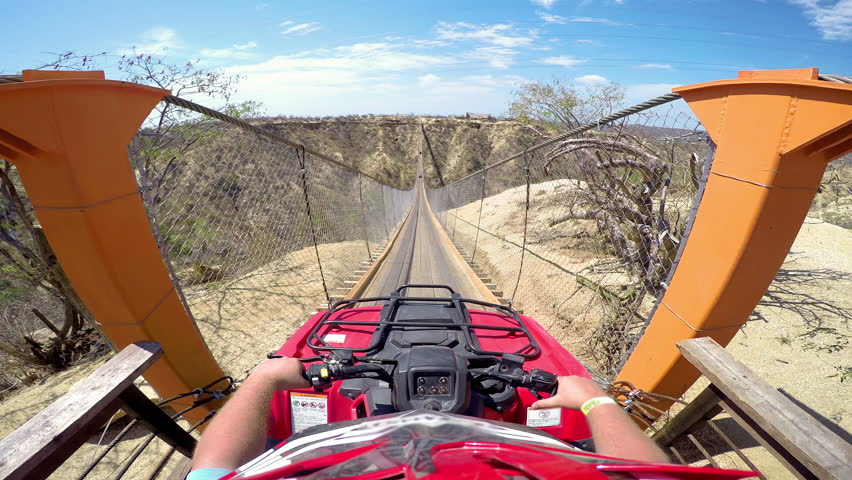 First person POV of a four wheeler driving across a hanging bridge | Shutterstock HD Video #12179018