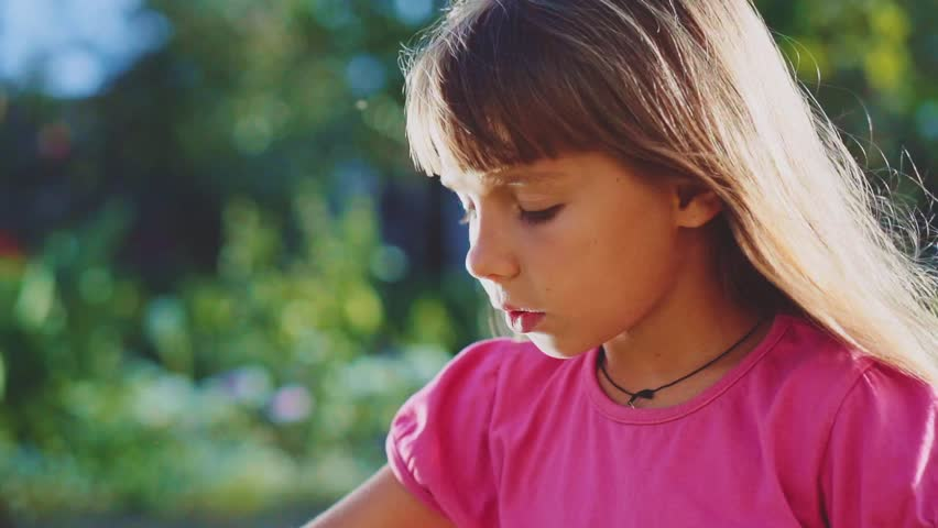Cute little girl is blowing soap bubbles in the garden outdoors on a sunny day. Slow Motion 240 fps. Happy childhood concept. Child is playing in bright sun light.  - HD stock footage clip