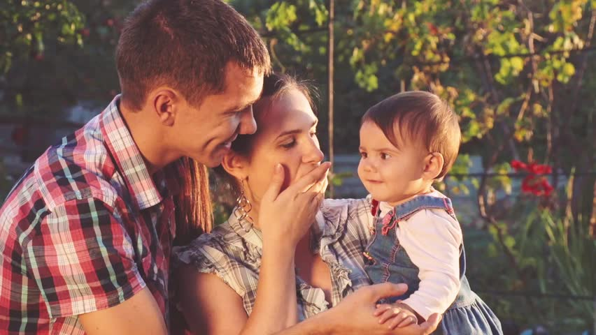 Young family: parents playing with their toddler daughter. Slow Motion 240 fps. Happy mother and father hugging their baby, smiling outdoors on a sunny day. Happy childhood and parenthood concept.  - HD stock footage clip