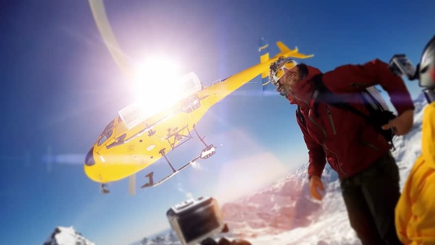 Actionsportlers were dropped by a helicopter at the top of the mountains. The sun is shining brightly in the blue sky. There is a mountain range in the background covered in snow. | Shutterstock HD Video #12186776