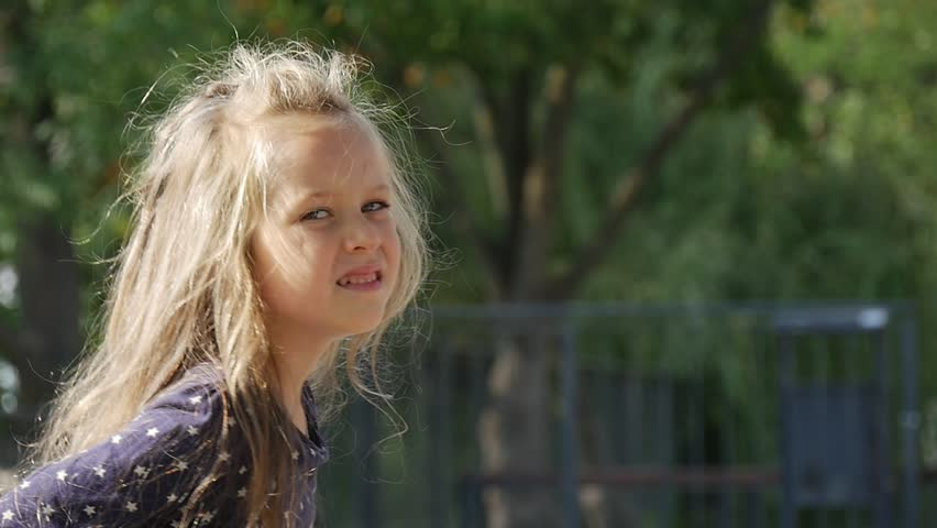 Little Girl Face Close up, With Long Fair Hairs and in Blue Blouse is Playing Ball is Standing Turning Looking Around Girl is Smiling, Jumping, Park Trees Fence on Background Sunny Day, autumn,   Shutterstock HD Video #12186794