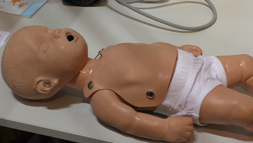 Woman's hand performing cardiac heart massage or CPR on a child mannequin