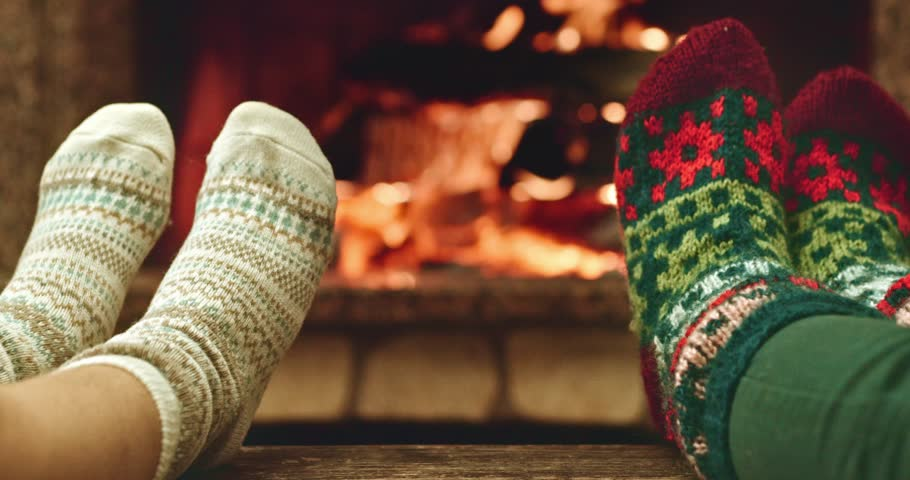 Woman Relaxes By Warm Fire In Woollen Socks And Having A