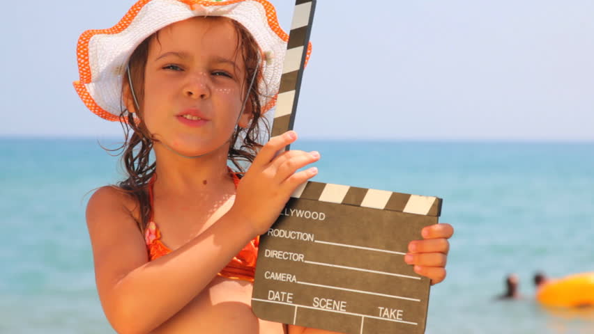 Nice little girl standing on seashore, something tells and clicks clapboard