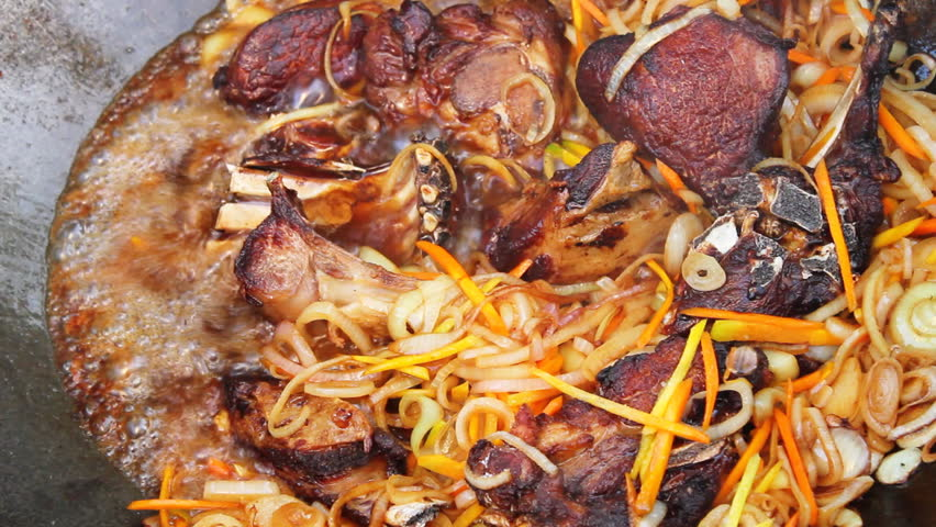 Meat frying with onion and carrots in campfire Cauldron. Closeup. - HD stock footage clip