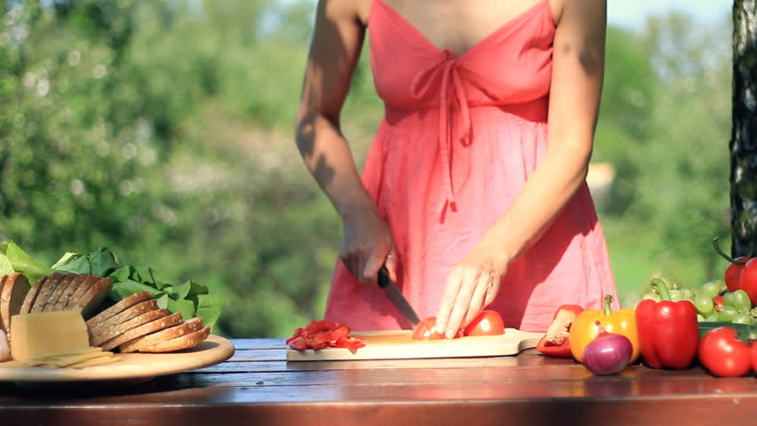 Female hands slicing tomato, outdoors, dolly shot  - HD stock video clip