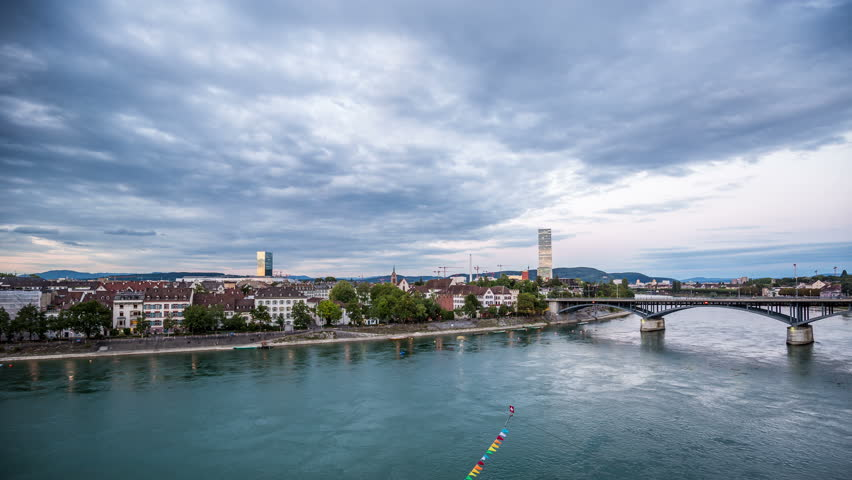 BASEL, SWITZERLAND – August 20, 2015: Basel skyline with, river, waterfront, sky with clouds in the evening timelapse, pan shot