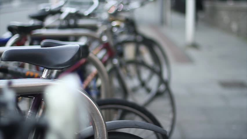 Medium shot of bicycle park, people walking on the background. - HD stock video clip