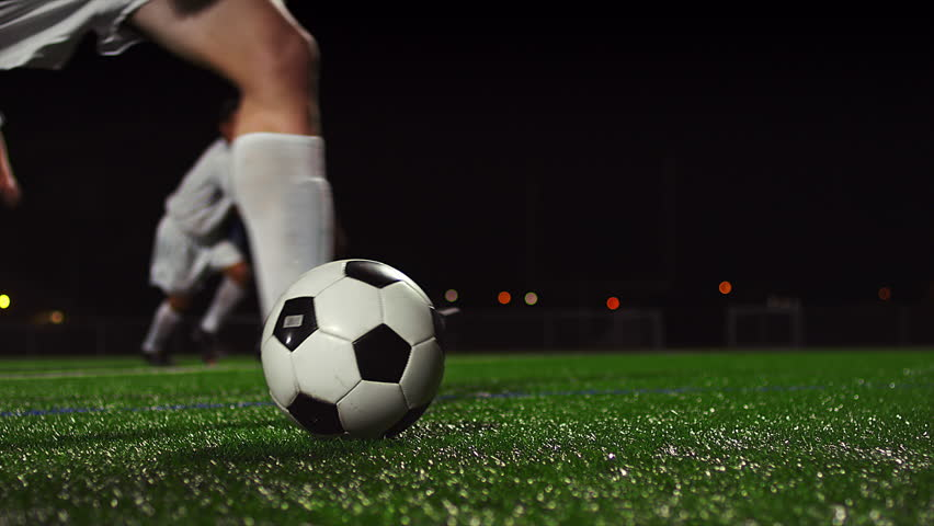 Close up of a soccer ball being kicked in slow motion at night
