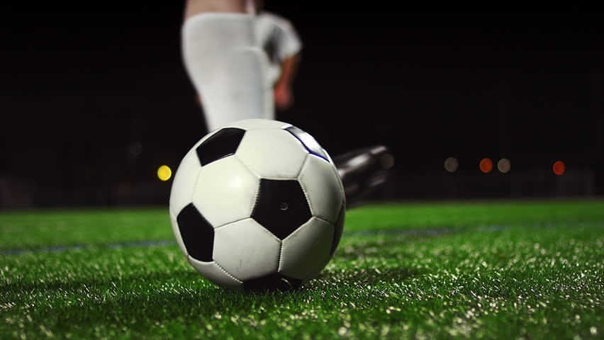 Close up of a soccer ball being kicked in slow motion at night - 4K stock footage clip