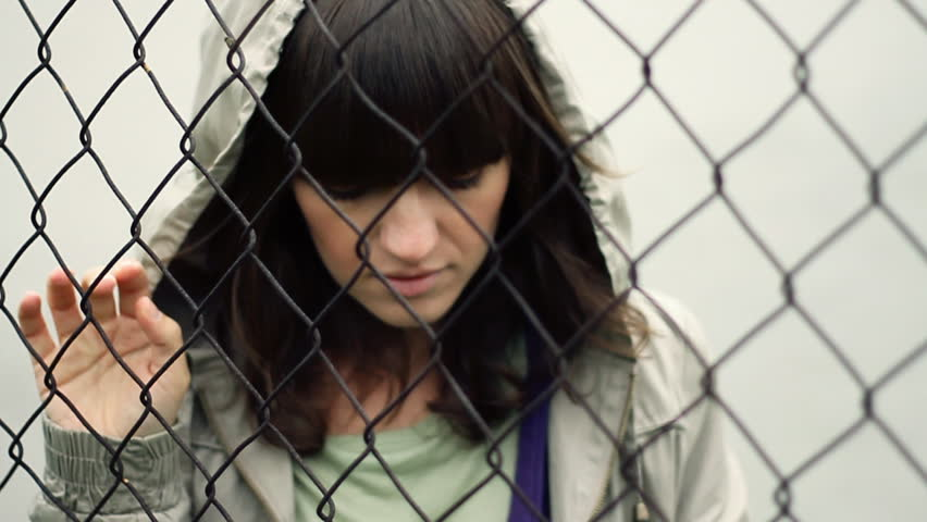 Sad woman behind chain-link fence, outdoors, slow motion