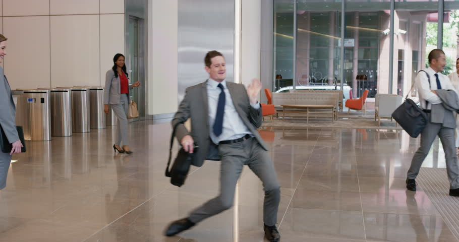 Crazy happy businessman dancing in corporate lobby wearing suit celebrating achievement