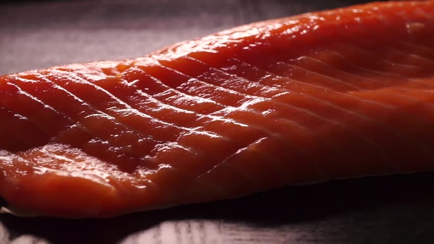 Salmon fillet rotating on a black table - HD stock footage clip