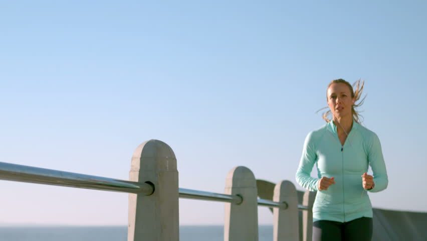 Smiling sporty woman doing a jogging at promenade | Shutterstock HD Video #12346994