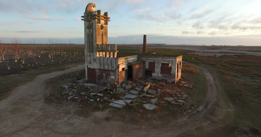 Aerial Drone scene of an abandoned Slaughterhouse at sunset, surrounded by dead trees in Epecuen at buenos aires argentina. Horrifying and scary exterior panorama. Camera flying close to sign.