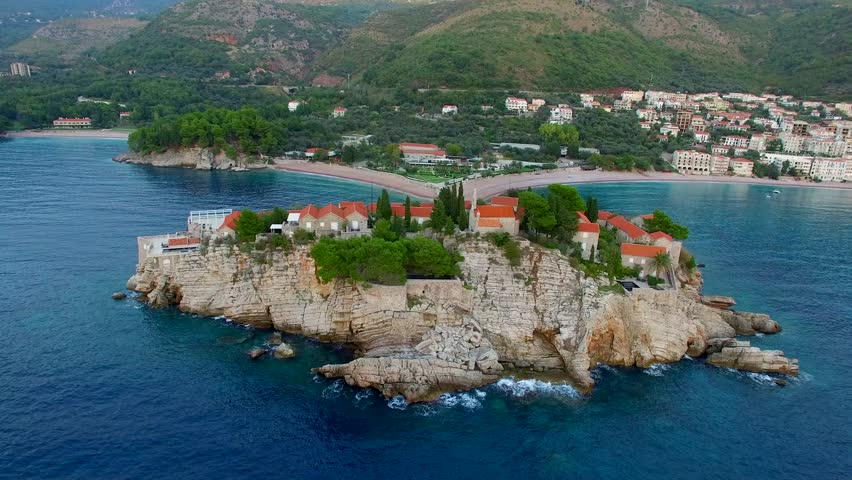 A helicopter flight over the island of Sveti Stefan in Montenegro. Aerial photography, video from a height, the height of bird flight. Flying over the sea, the coast and the Balkans - 4K stock footage clip