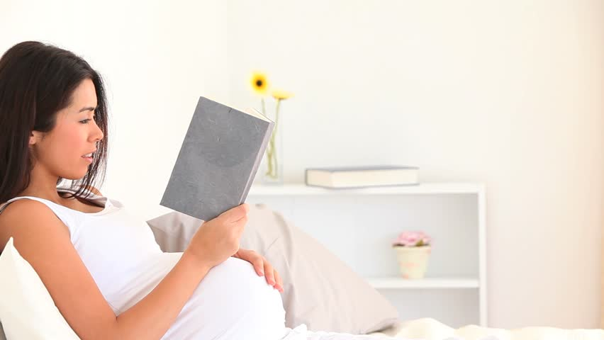 Pregnant woman reading a book in her living room