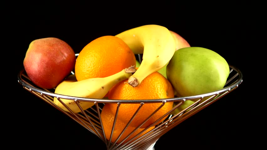 Fruits in vase like banana, apple, orange, taking by two persons, on black background - 4K stock video clip