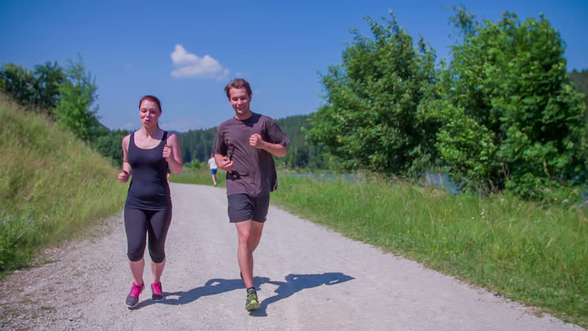 EVENT JUNE 2015 LUKOVICA: Two young people are running around the lake and then the lady stops because she can't run anymore. The scenery is beautiful. We can see the water in the background. - HD stock footage clip