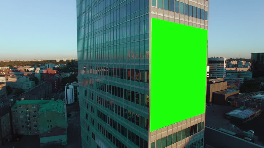 Aerial Orbit Shot of Glass Office Building With Green Screen Mock-up of Billboard in Business District. #12581273