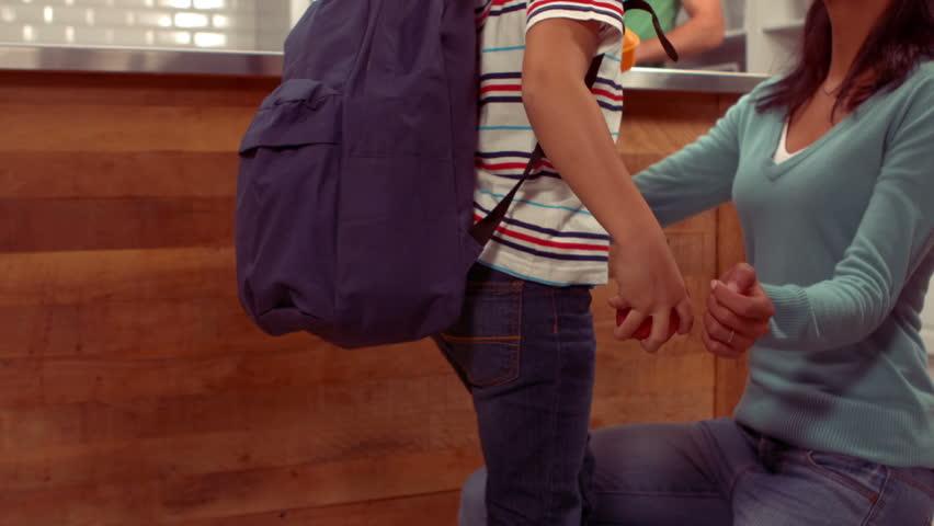 Smiling Hispanic boy saying goodbye to his family at home