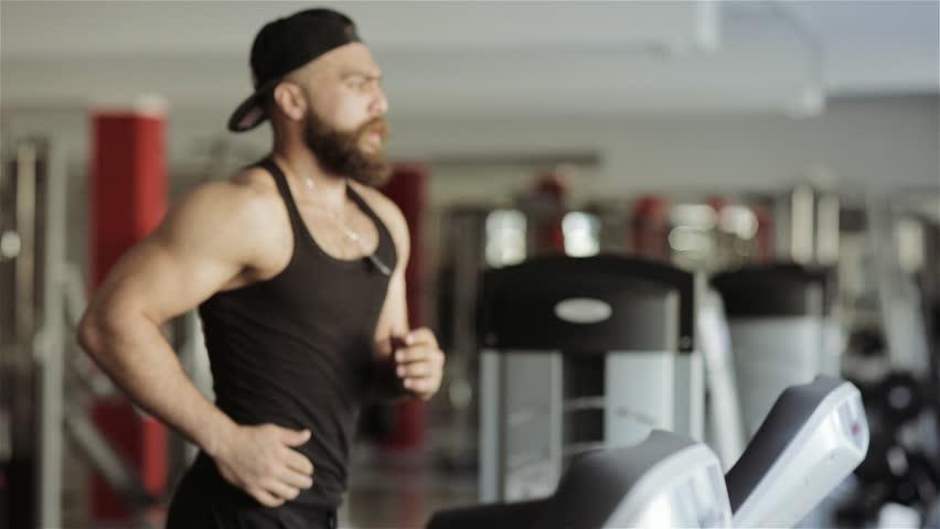 A man runs on a running machine in the gym