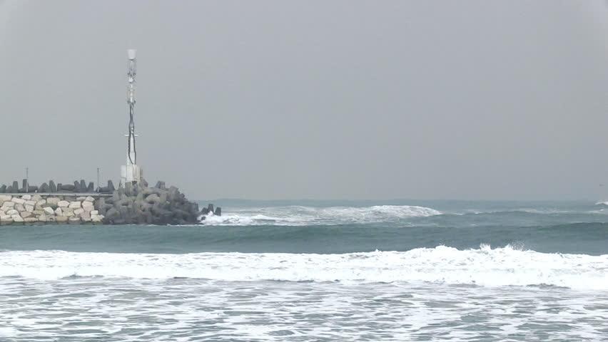Extreme waves crushing coast with lighthouse on the background.
