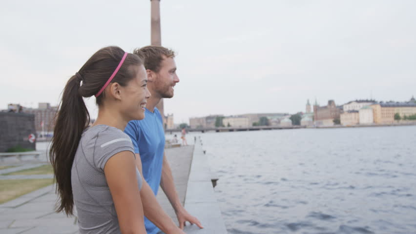 Smiling sporty couple looking at sea view. Happy man and woman in sportswear are standing on footpath. Side view of young male and female against sky. Stockholm, Sweden, Europe. #12642860