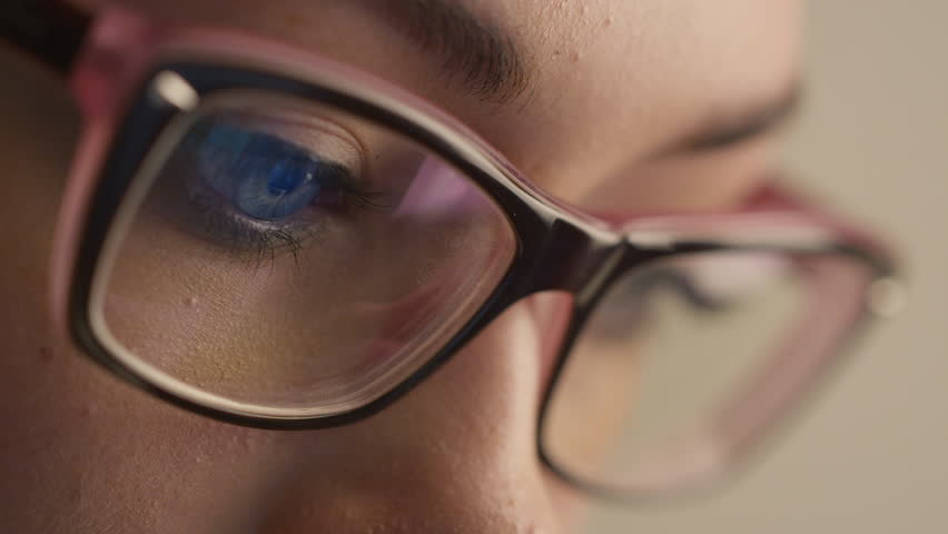 Close-up shot of woman eyes in glasses reflecting a working computer screen. Shot on RED Cinema Camera in 4K (UHD).