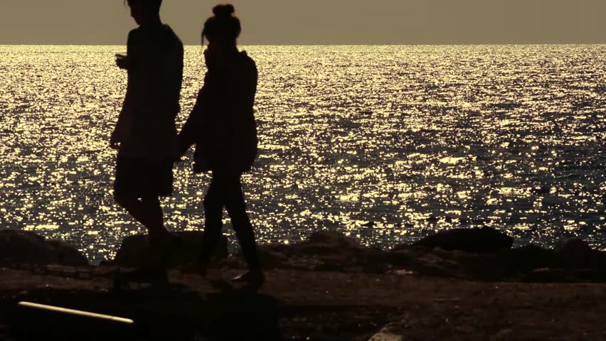 Boys walking by the sea at sunset - HD stock video clip
