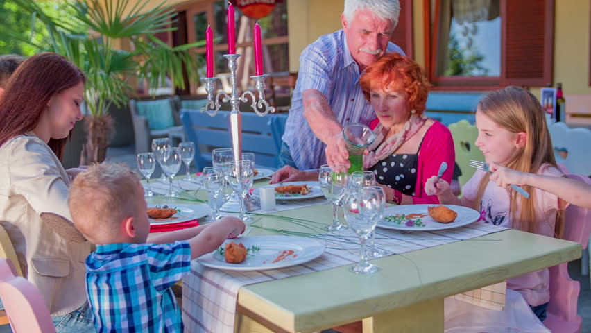 A family is sitting by the table and the grandfather stands up and is pouring some water into his grandchildren't glasses. The day is sunny. Close-up shot. - HD stock footage clip