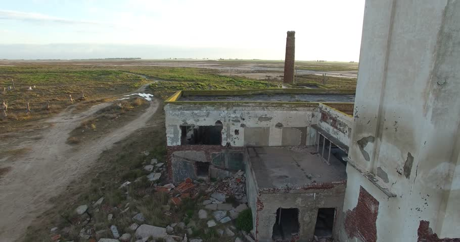 Aerial Drone scene of abandoned Slaughterhouse at sunset, surrounded by dead trees in Epecuen, buenos aires. Camera traveling close to the buildings sign.