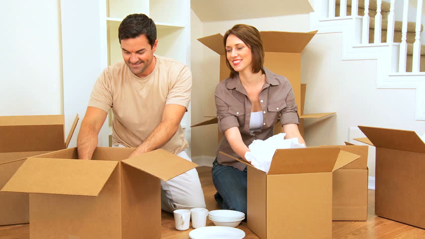 Attractive caucasian couple fooling around with packing materials from new house move - HD stock footage clip