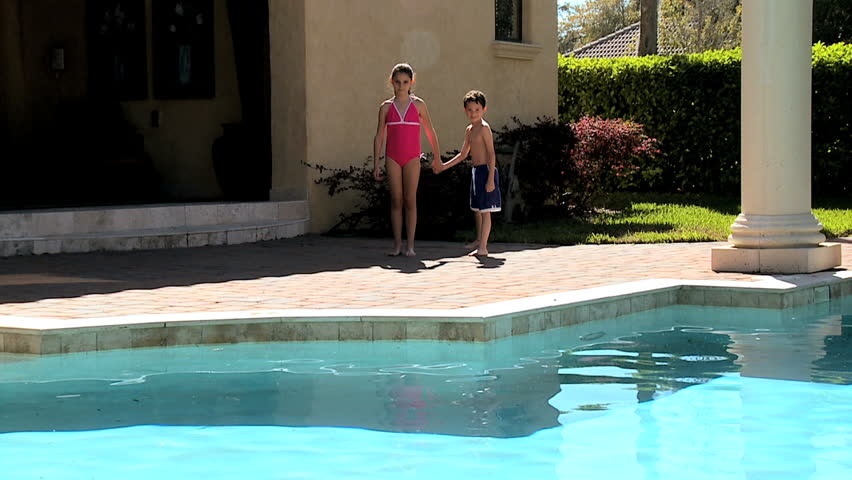 Caucasian siblings jumping into the family swimming pool - HD stock footage clip