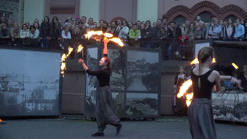 VILNIUS, LITHUANIA - JUNE 19, 2015: Young women with burning torches perform spectacular fire juggle show for people audience on June 19, 2015 in Vilnius, Lithuania. Panorama shot. 4K