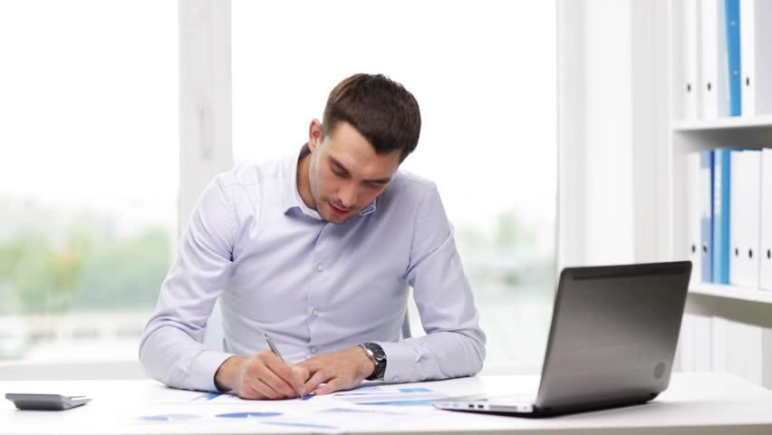 Businessman Using Calculator And Laptop Computer Stock