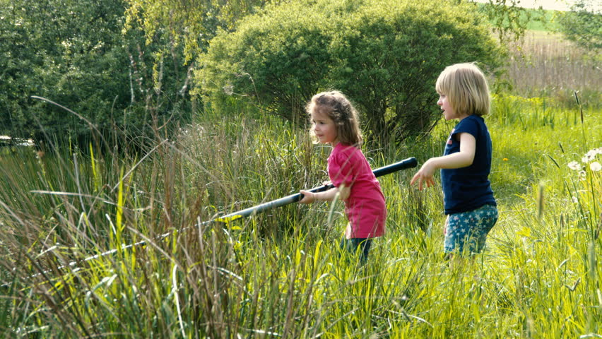 Two kids boy and little girl sit near pond and play with for Little girl fishing pole