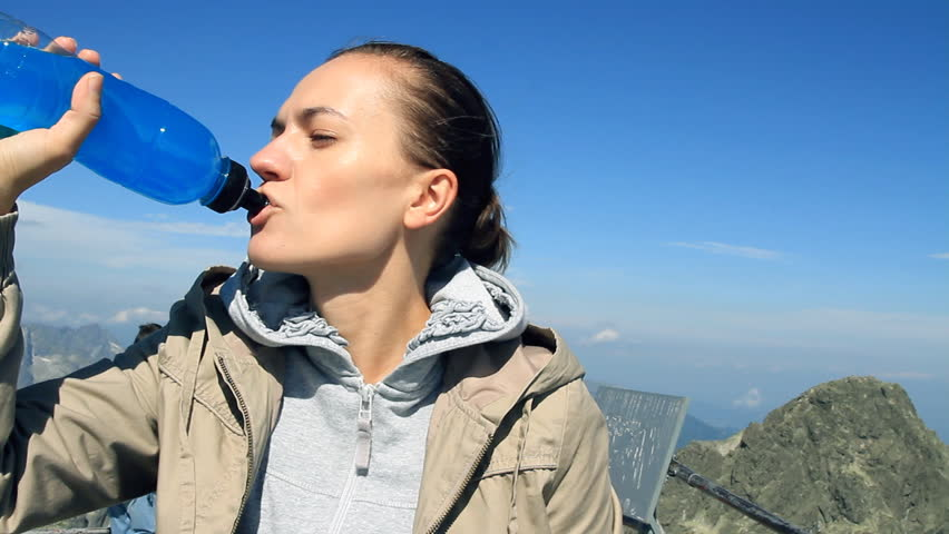 Female hiker drinking isotonic drink in the mountains, camera stabilizer shot  - HD stock video clip