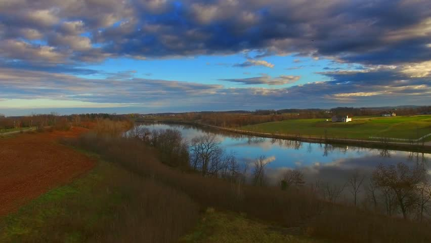 Dramatic rural midwest landscape with morning sky reflected in calm river, aerial flyover.