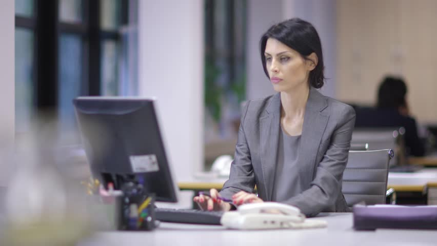 Women as business leaders. Woman In Business Suit. Sitting in an office at her desk working late, Paperwork - HD stock footage clip