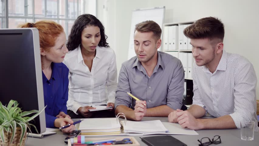 Group of Four Young Business People Discussing Something on Documents at the Table Inside the Office. - 4K stock footage clip