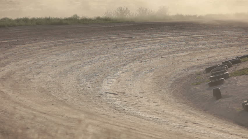 Race cars on dirt oval course spread out following each other. Highly modified stock cars driving and racing on a very dirty and dusty track corner. High speed around dusty corner.  - HD stock footage clip