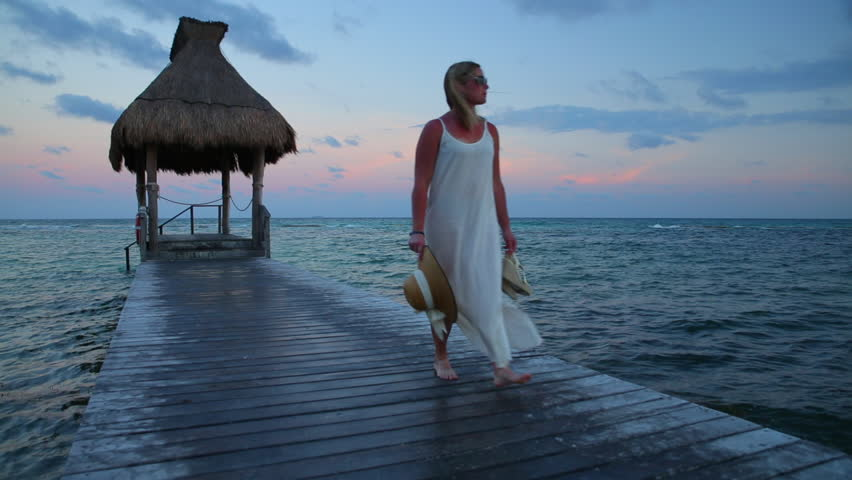 Cinemagraph - Woman walks down pier at tropical resort. Looping Motion Photo.