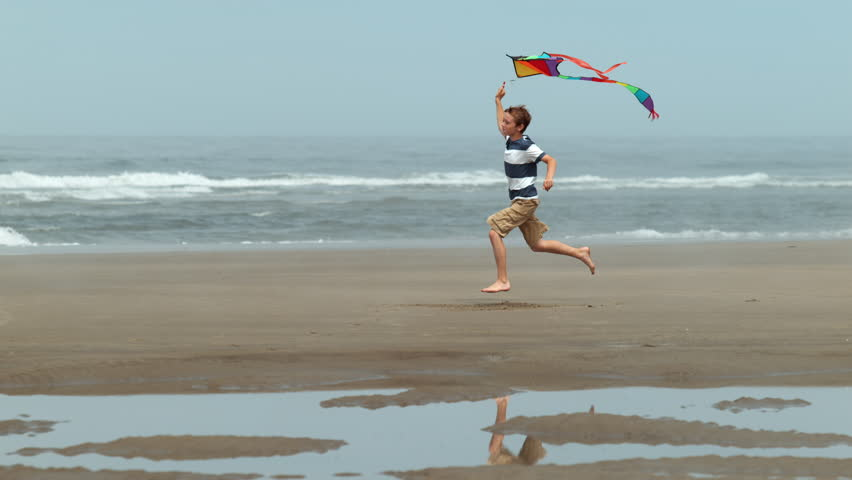 Cinemagraph - Boy running with kite at beach, slow motion. Looping Motion Photo.