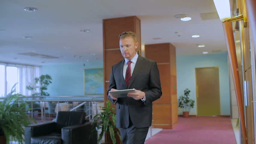 The businessman in a strict suit goes along the corridor and holds the tablet in hands. The man is very serious. In slow motion - HD stock video clip