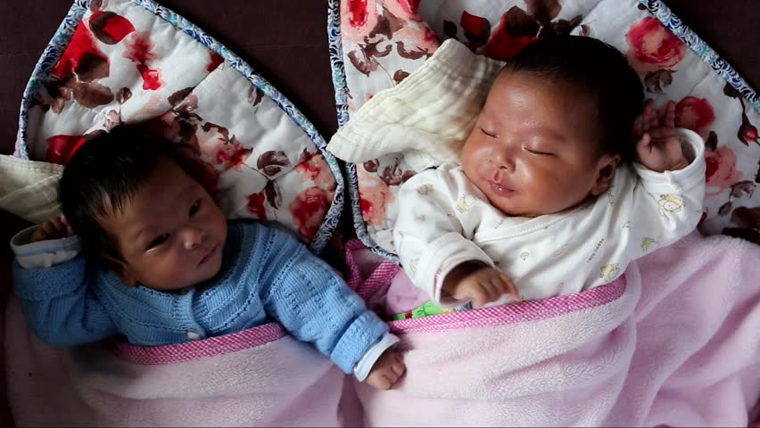 Cute boy and girl twins babies lying on the bed - HD stock video clip