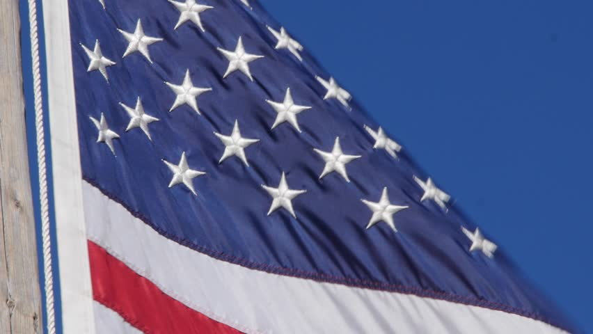 A beautiful American flag blows in a strong wind against a blue sky backdrop - 4K stock footage clip